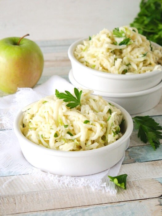 Two bowls of creamy Apple Jicama Slaw on a wooden table.