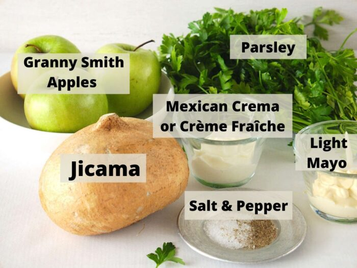 Labelled Ingredients for Creamy Green Apple Jicama Slaw include green apples, Mexican crema, jicama, salt & pepper, mayonnaise and parsley.