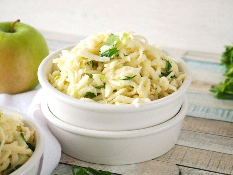 Mexican Jicama Slaw in a white bowl on a wooden table.