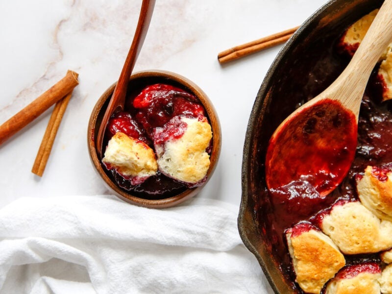 skillet with plum cobbler and a bowl of plum cobbler