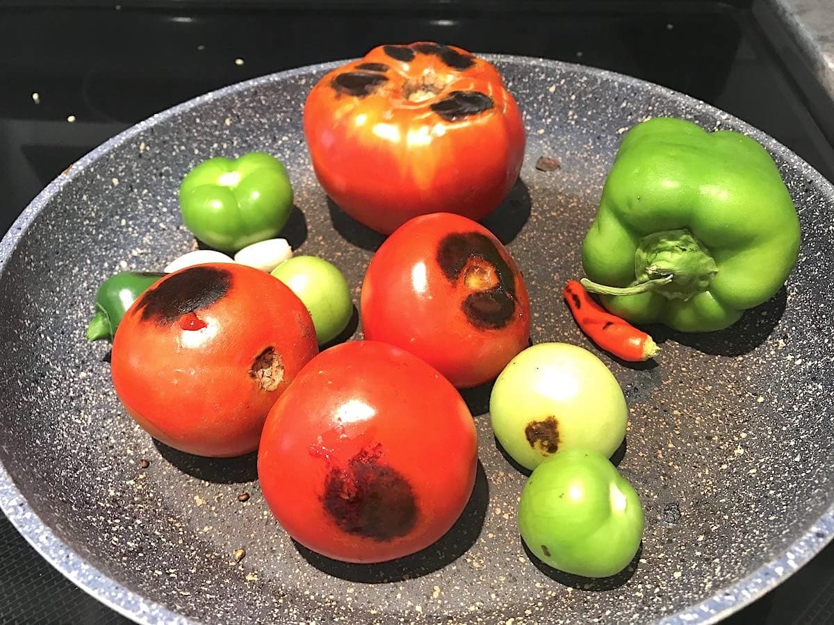 Pan-roasting tomatoes in a skillet for salsa.