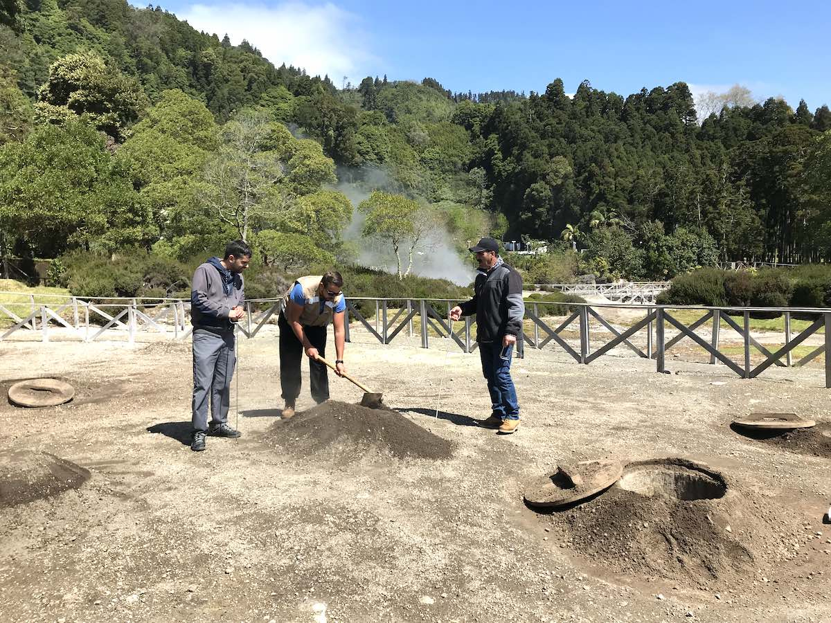 Men cooking the local dish cocido within the volcanic ovens buried underground on Sao Miguel Island Azores.