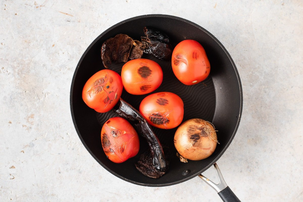 Chile guaque, chile pasa and Roma tomatoes in a skillet.