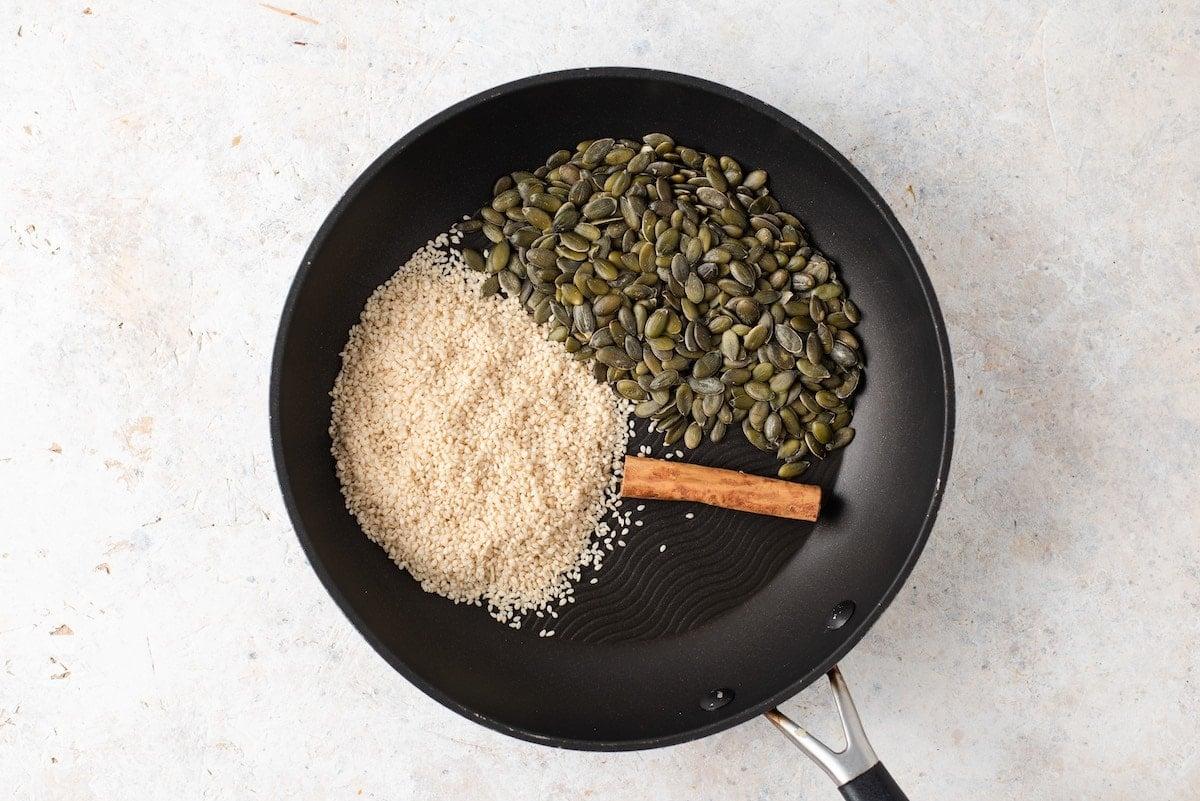 Pumpkin seeds, cinnamon and sesame seeds in a skillet.