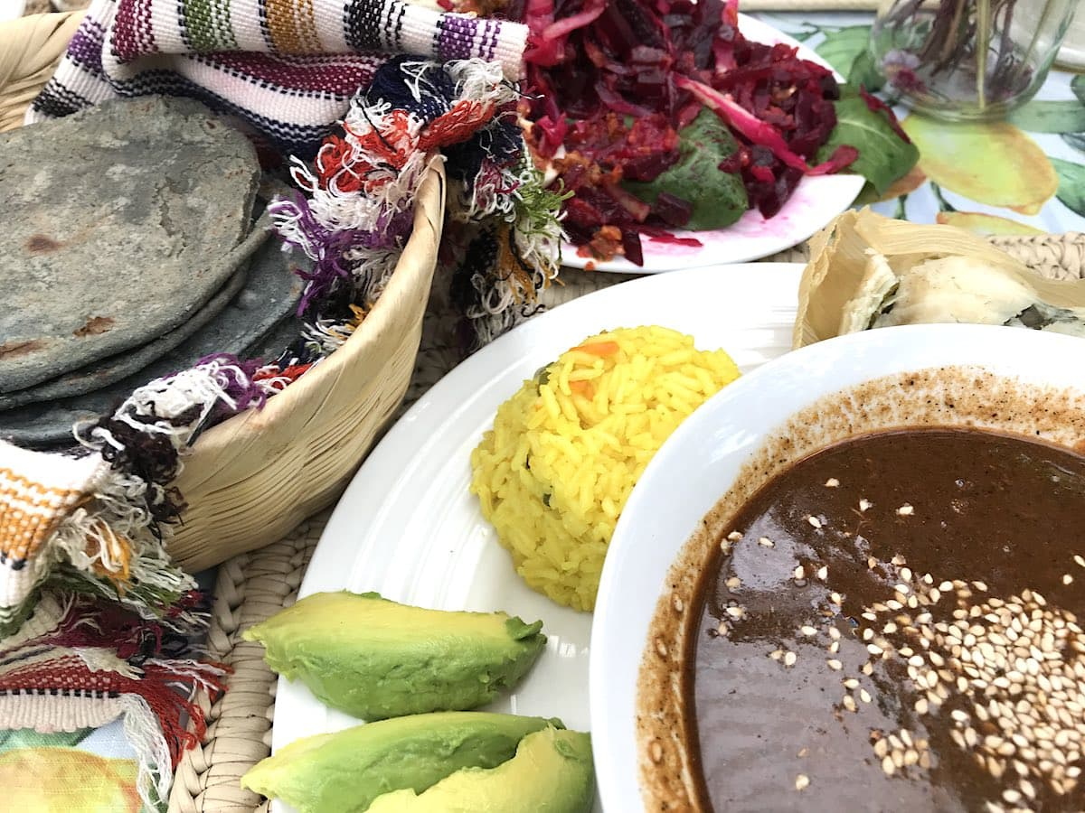 Pepian, blue corn tortillas, rice and avocado on a plate at Sabe Rico restaurant in Antigua Guatemala.
