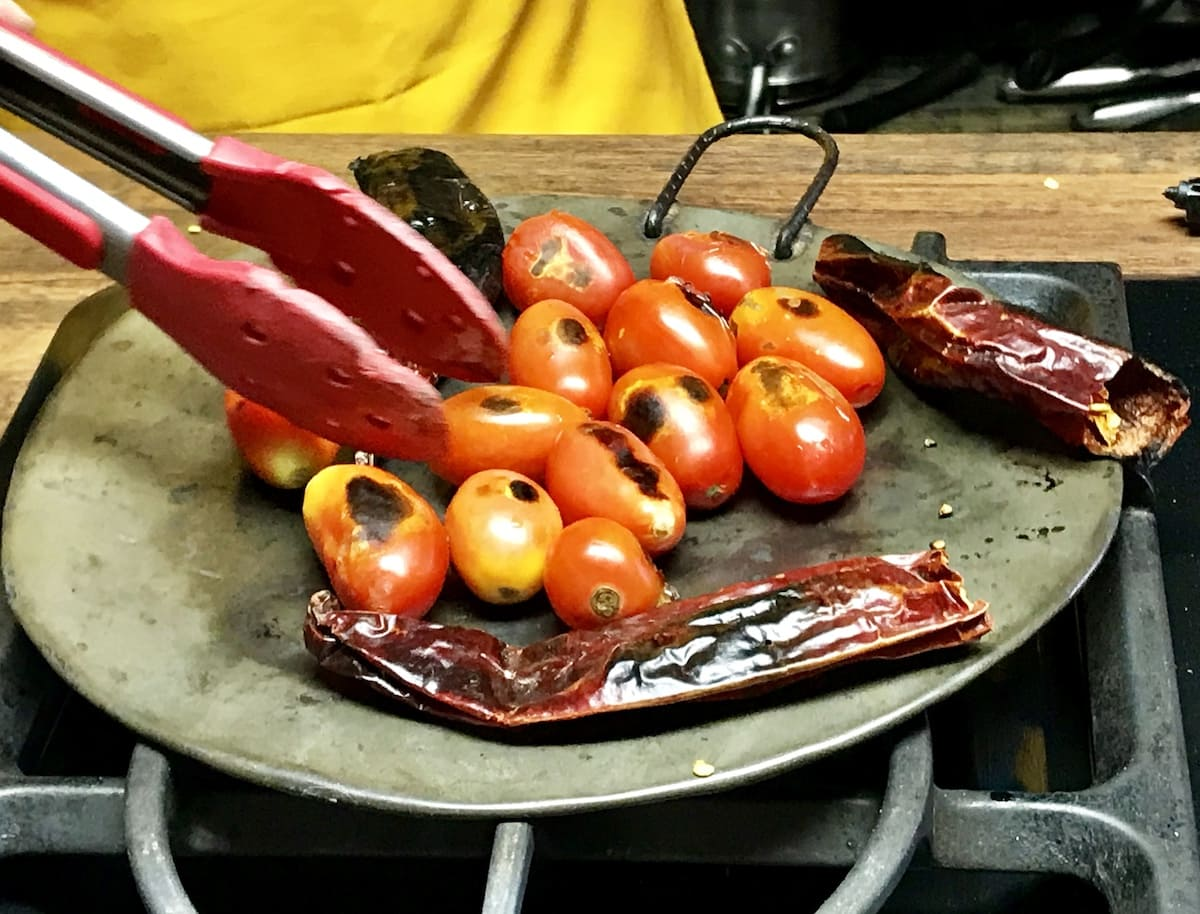 Charring tomatoes and guaque chile on a comal in Guatemala. To