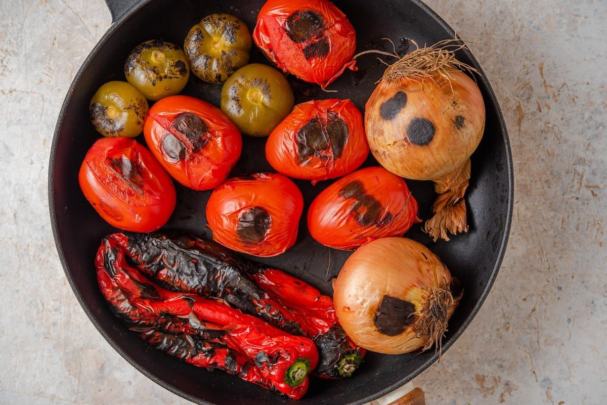 Charring tomatoes, peppers, onion and tomatillos in a skillet.