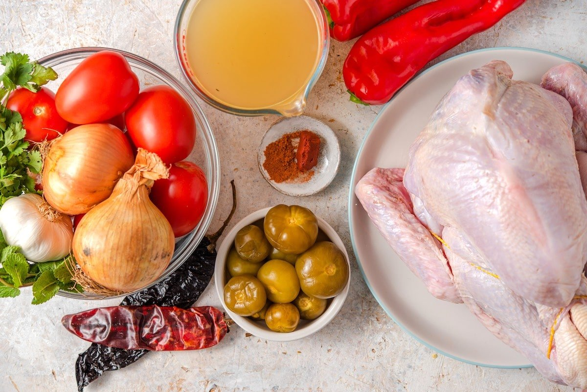 Ingredients for kak'ik turkey soup include turkey, tomato, tomatillos, broth, cobanero chile, tomato, onion, red peppers, achiote and tomatoes.