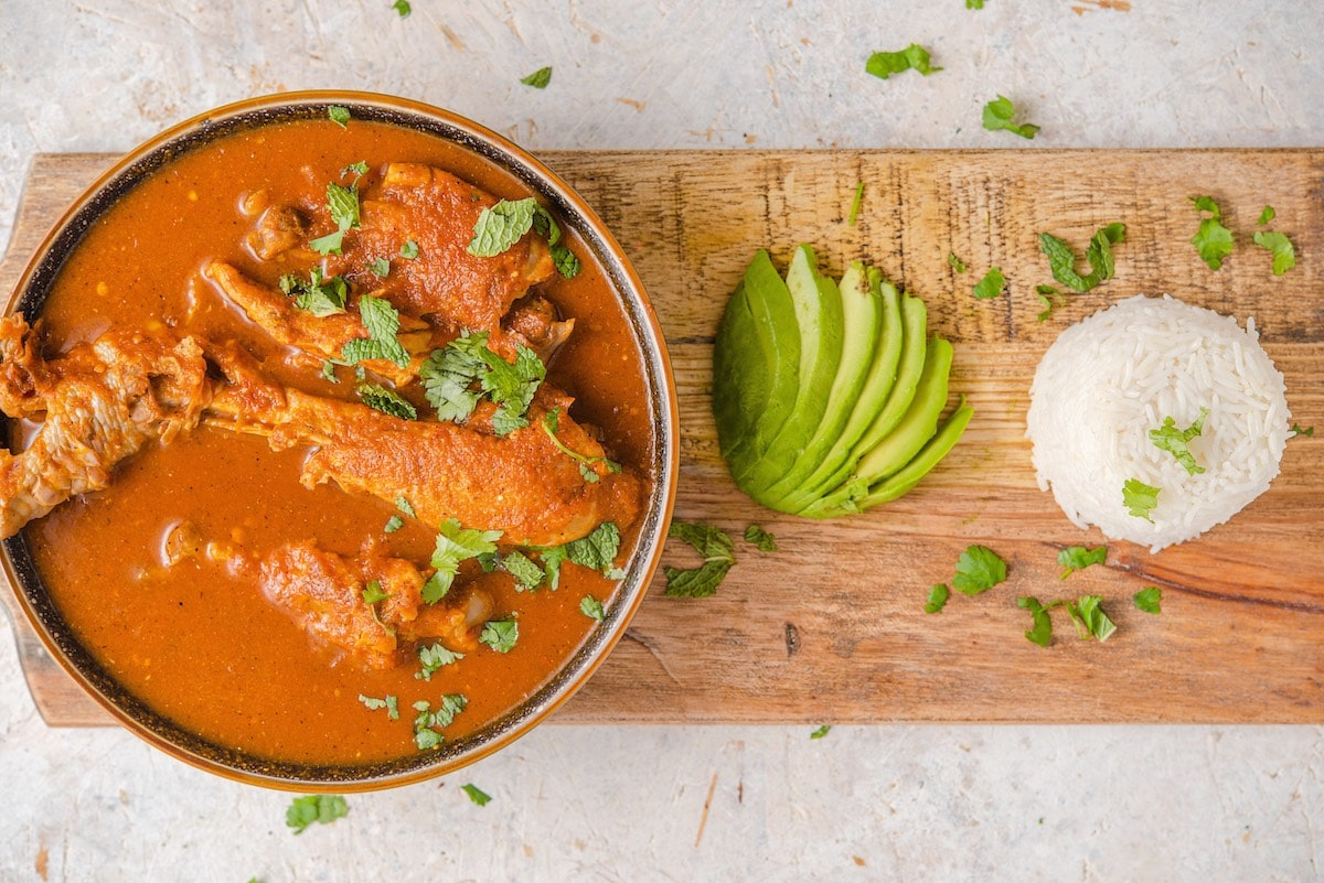 Guatemalan kakik de pavo on a wooden board with white rice and sliced avocado.