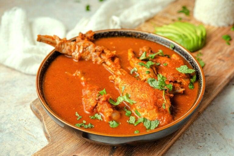Kak ik Guatemalan turkey soup in a pottery bowl on a board.