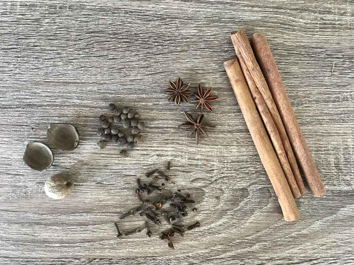 Cinnamon sticks, whole cloves, allspice, star anise and nutmeg on a wooden table.