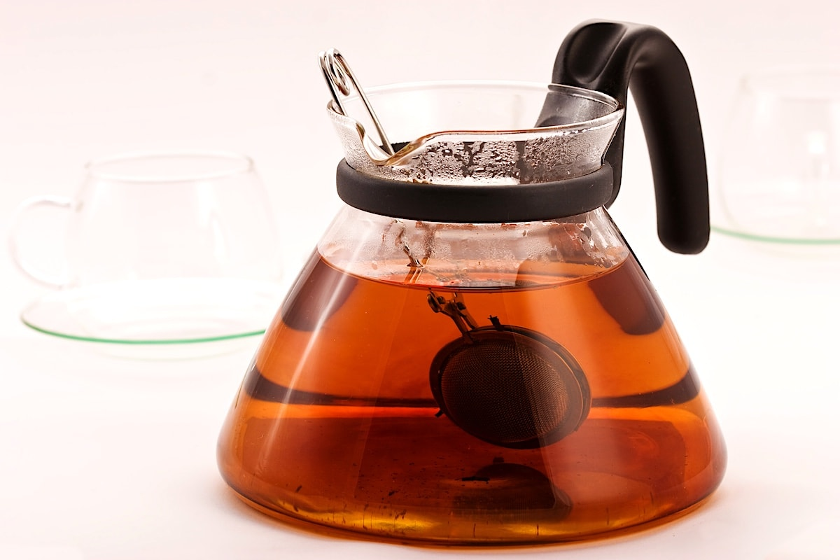 Black tea steeping in a clear glass pot.