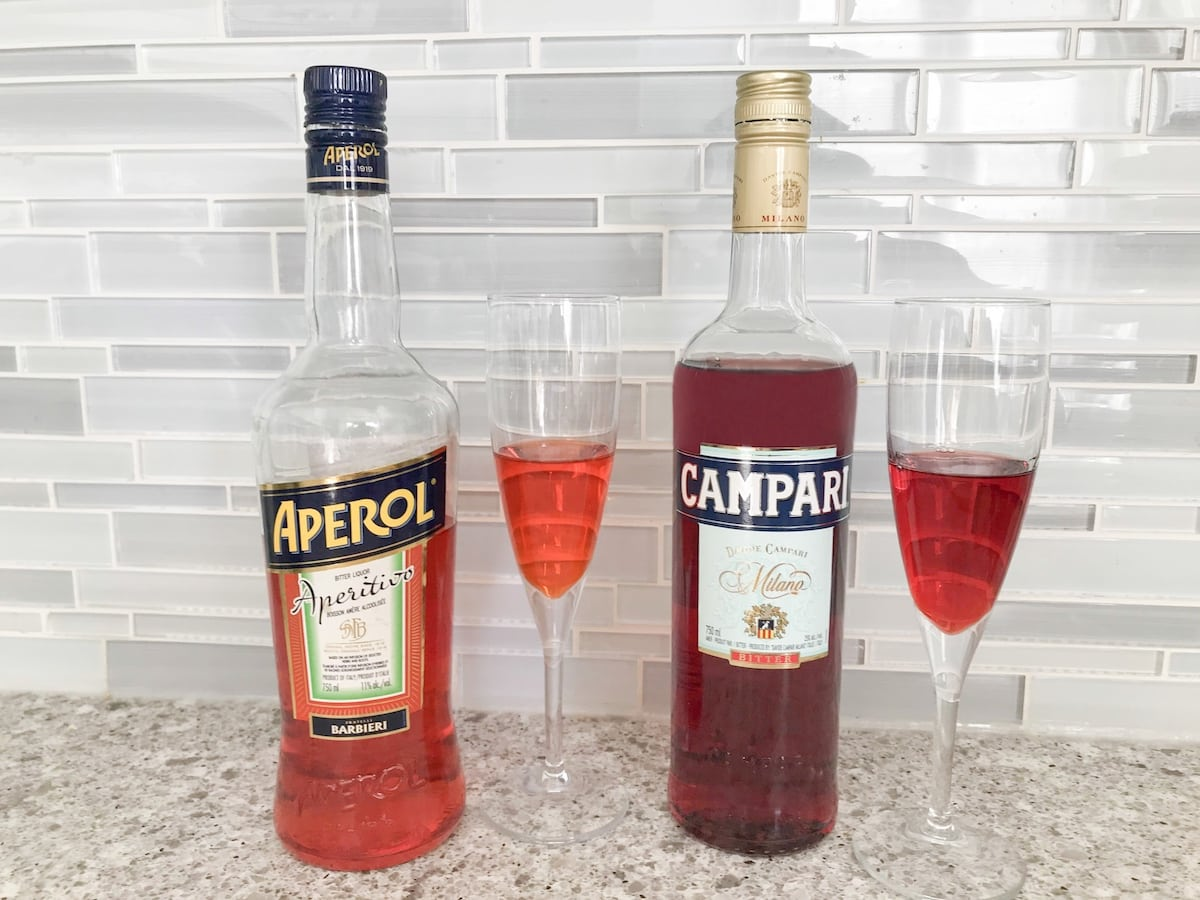 Differences in colour between orange Aperol and Red Campari demonstrated on two bottles and glasses of alcohol.