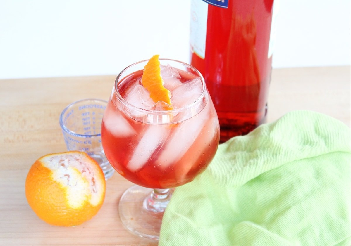 Orange, a bottle of Campari and a cocktail with a green napkin on a countertop.