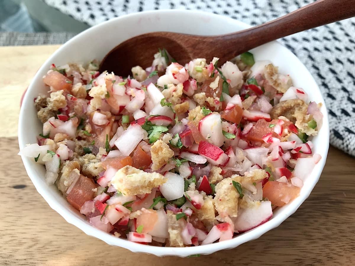 A white bowl of Guatemalan chojin, pork rind and radish salad.