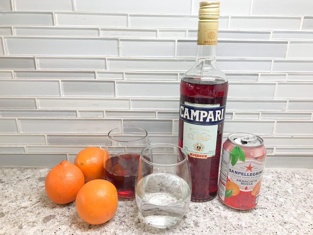 Campari, pomegranate juice, vodka, oranges and San Pellegrino sparkling drink on a countertop.
