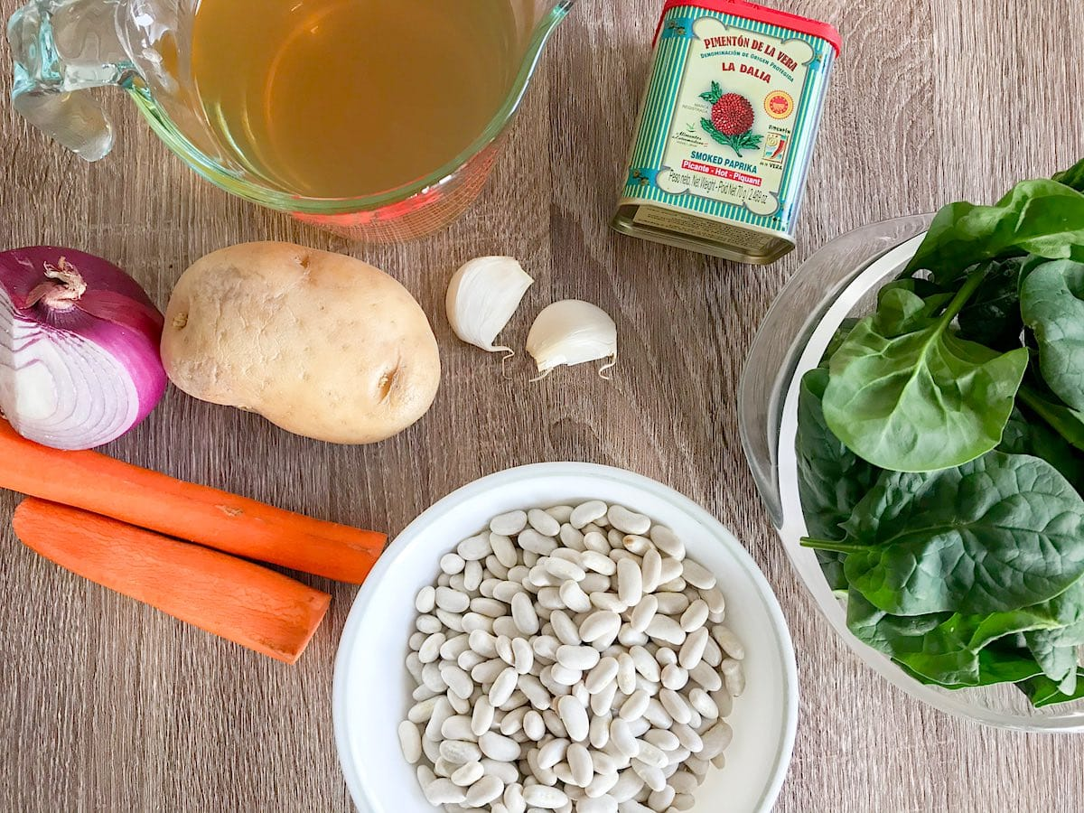 Ingredients for White Bean Soup including carrot, potato, red onion, garlic, vegetable broth, smoked paprika, baby spinach and white kidney beans on a wooden table.