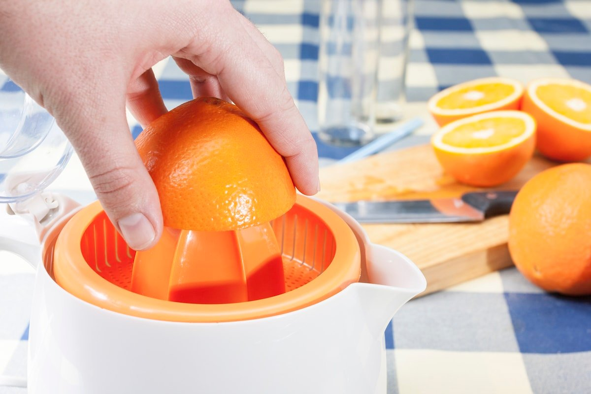 Squeezing oranges in a white juicer.