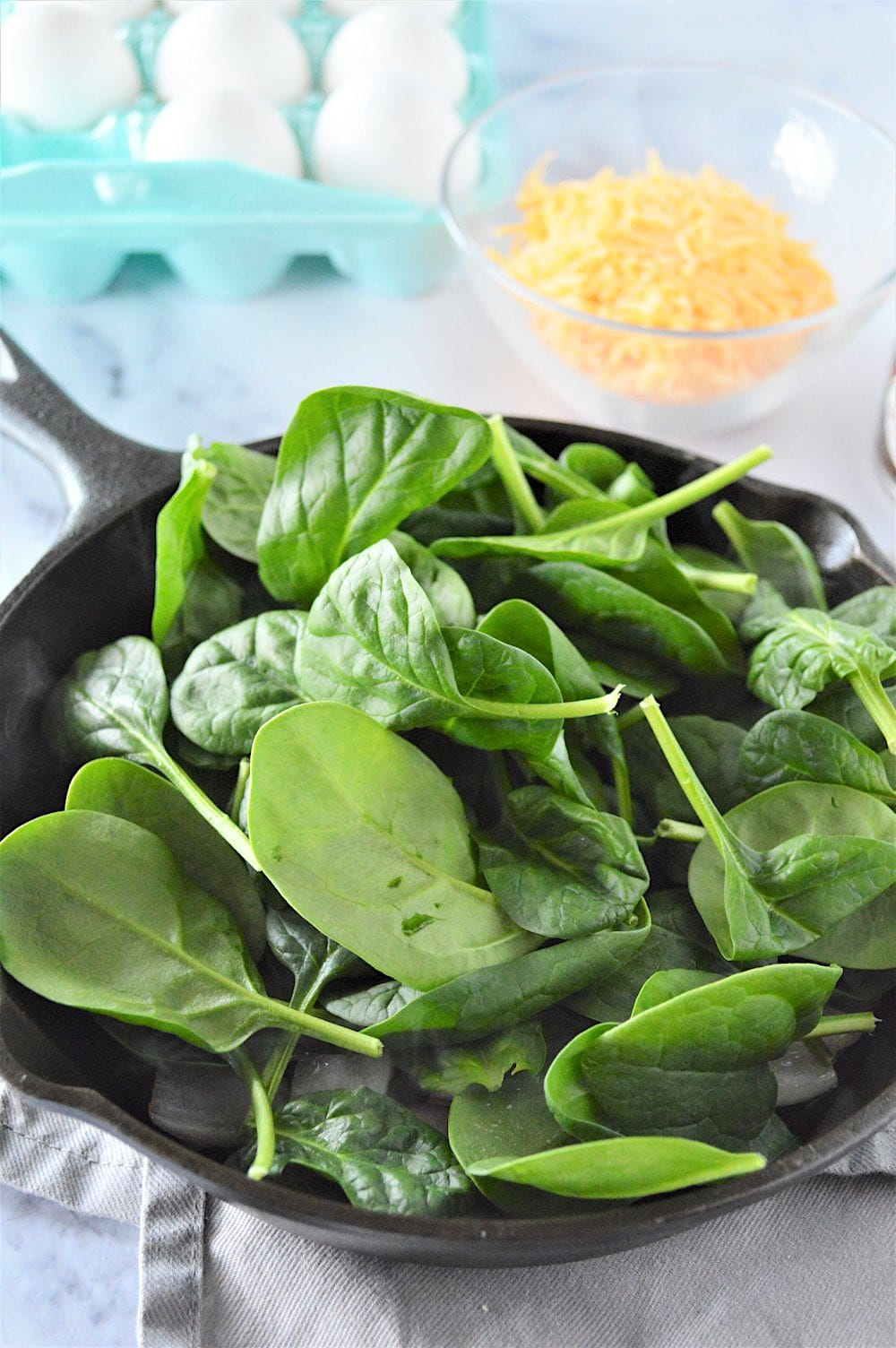 Spinach cooking in a skillet until wilted.