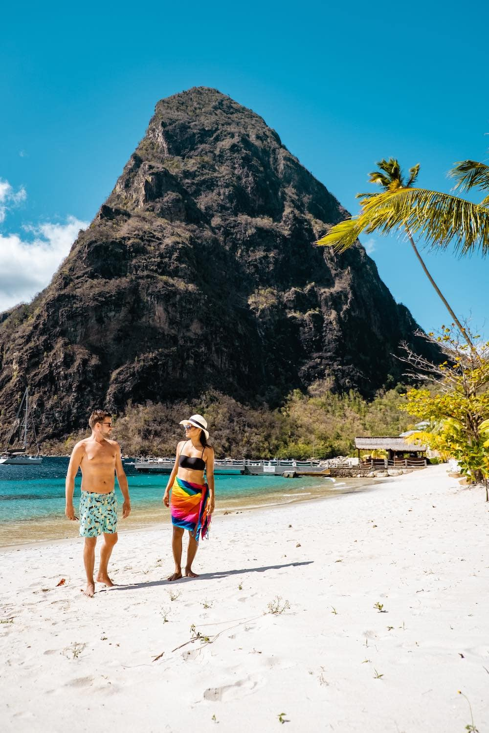 Couple walking on a beach in St. Lucia holding hands on a Caribbean honeymoon.