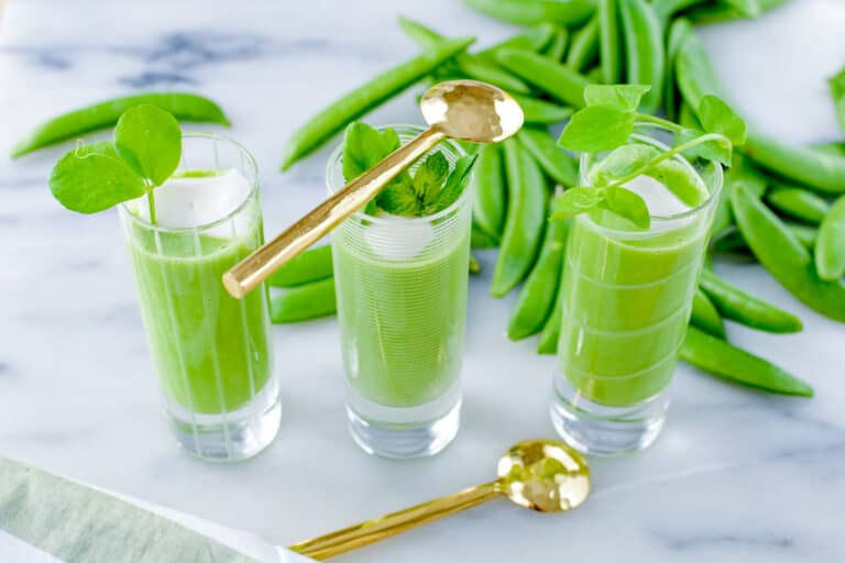 Chilled pea soup shooters with gold spoons.