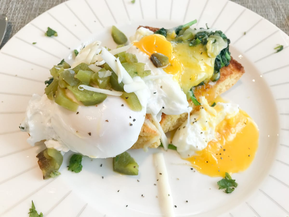 Cornbread topped with two eggs and green chiles.