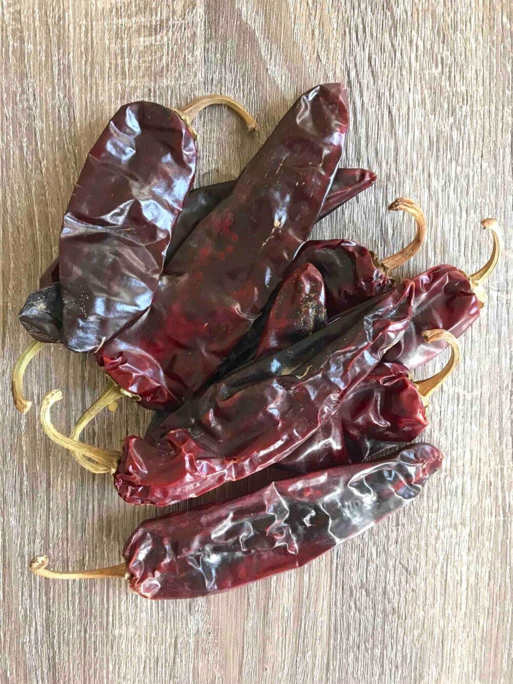 Guaque or guajillo chilis on a wooden table.