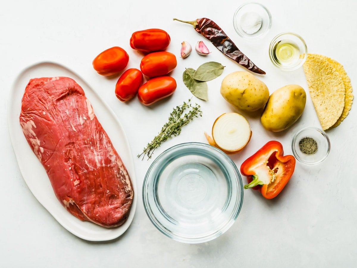 Overhead shot of ingredients for hilachas including flank steak, garlic, onion, tomatoes, red pepper, potato, chile, salt, pepper, thyme and bay leaf.