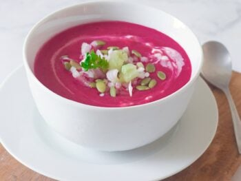 Healthy beet gazpacho with yogurt in a white bowl.