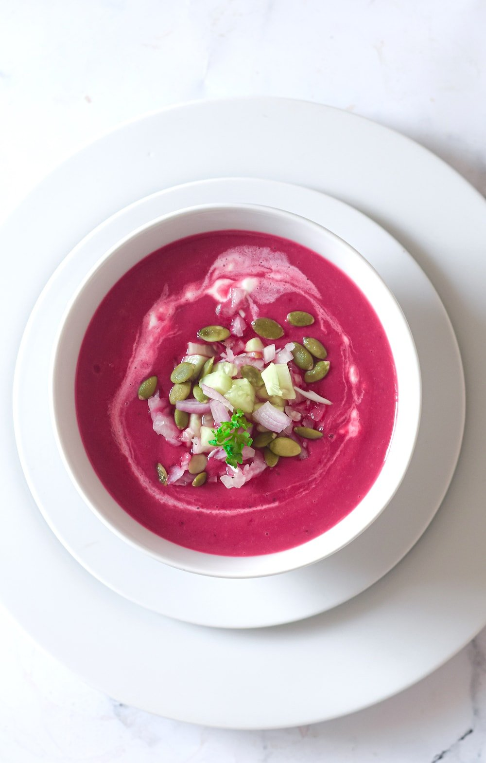 Overhead shot of gazpacho de remolacha or chilled beet soup in a white bowl.