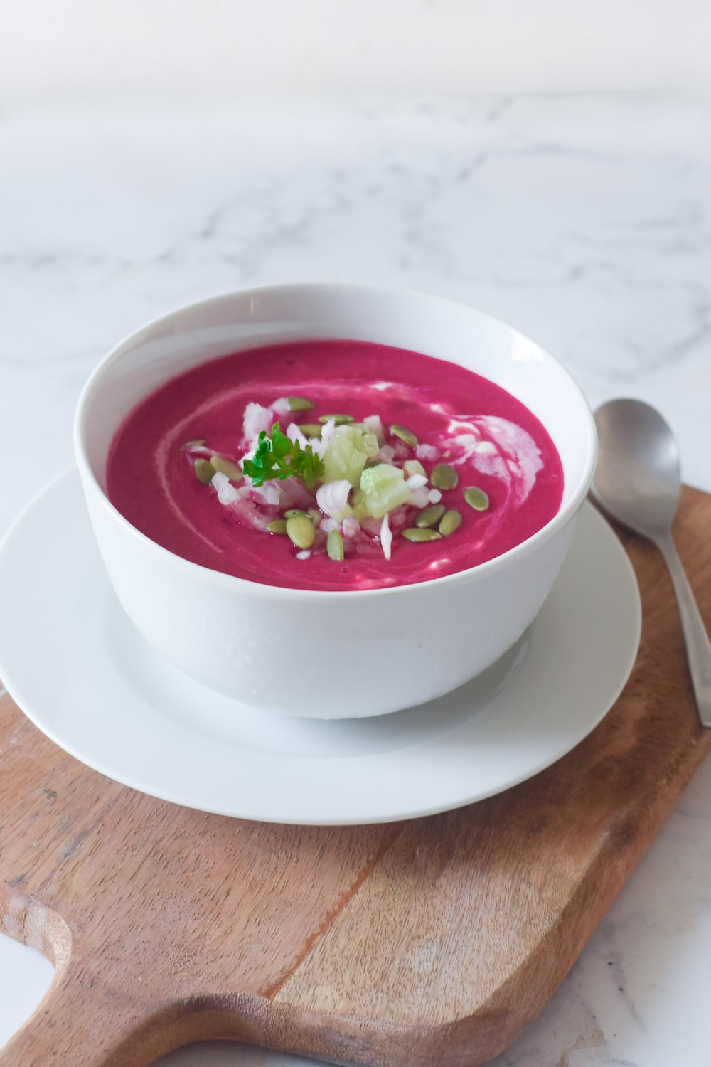 Beet gazpacho soup in a white bowl on a wooden board.