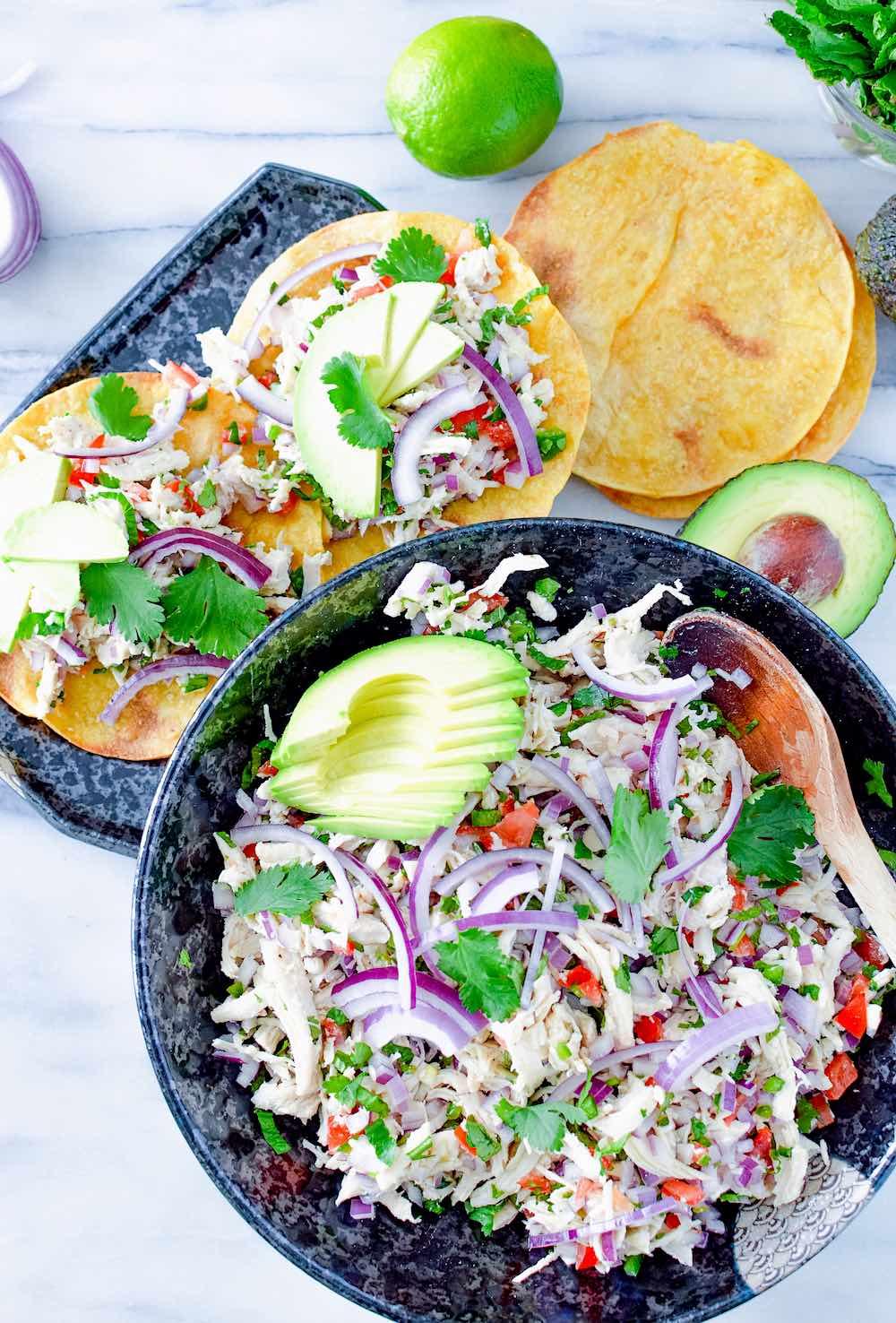 Guatemalan salpicon de pollo in a bowl and on crispy tostadas.