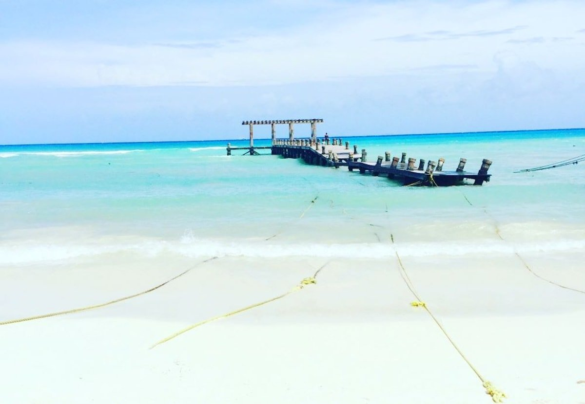 Dock in blue water in Playa del Carmen Mexico.