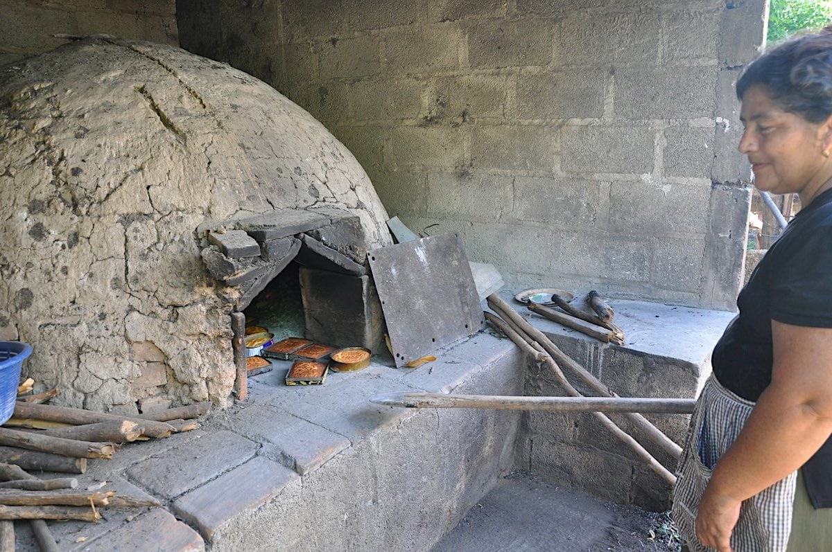 Woman baking quesadilla cakes in an outdoor oven in Zacapa, Guatemala.