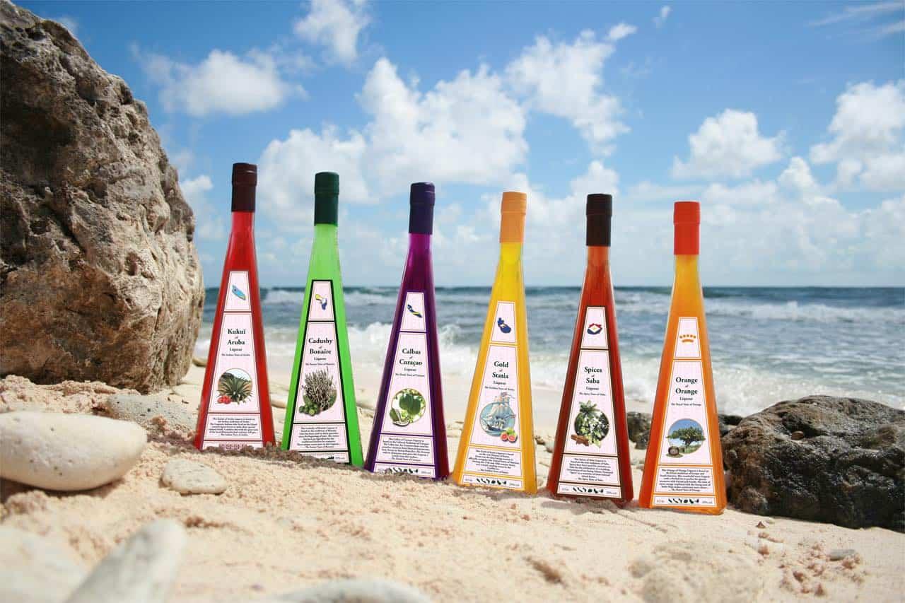 Bottles of Cadusht Liqueurs set on an ocean shore.