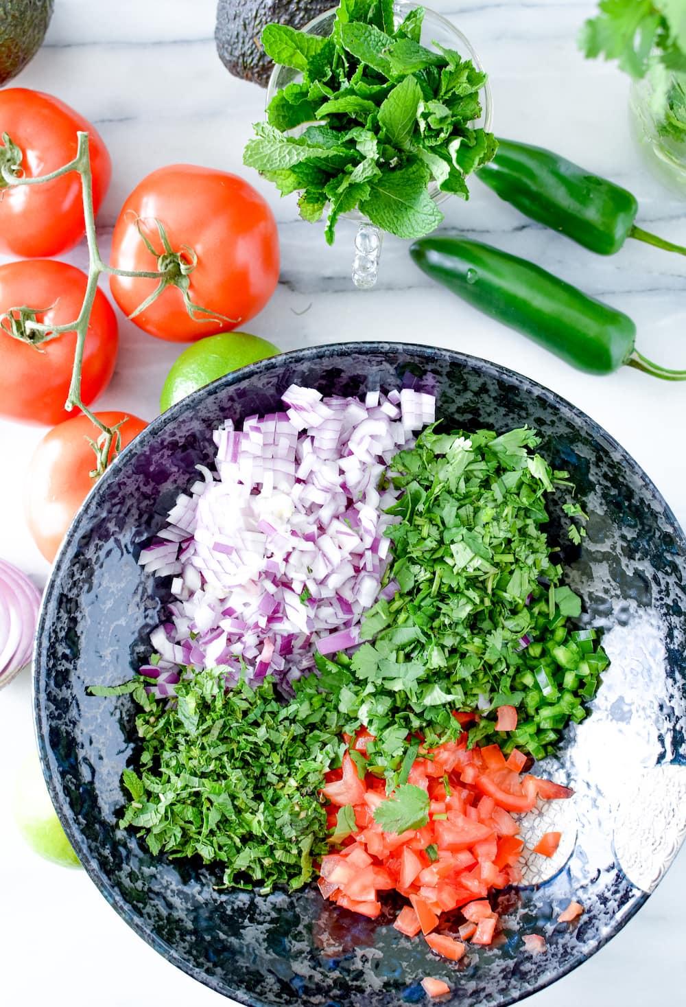 Chopped tomato, cilantro, radish, onion and mint in a bowl.