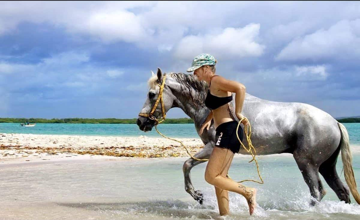 Woman and a horse beside the sea horseback riding in Bonaire, Dutch Caribbean.
