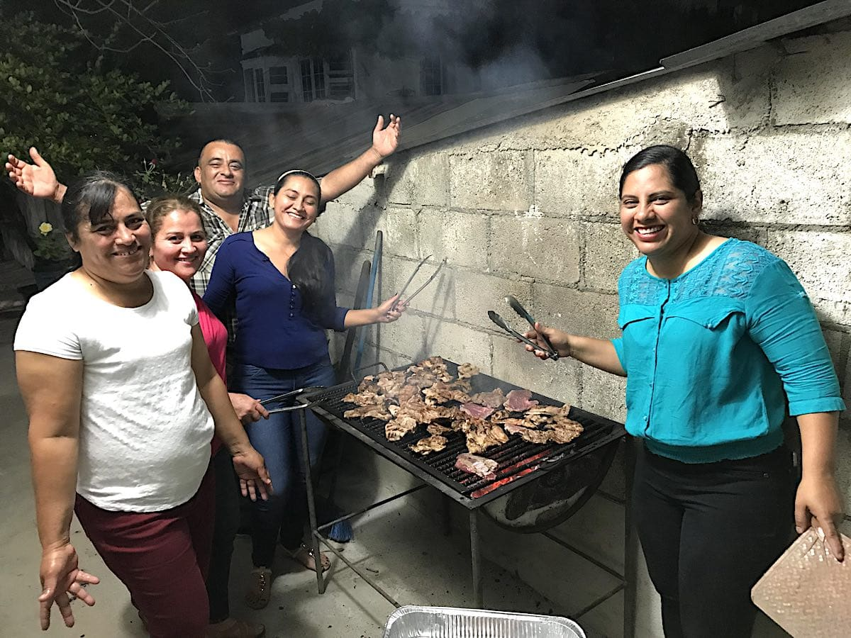 People grilling meat over charcoal at a party is a good example of Guatemalan food culture.