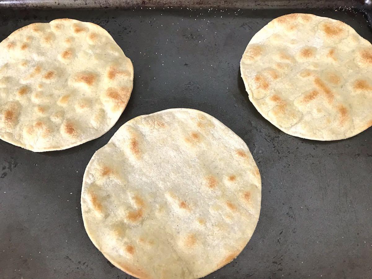 Homemade baked tostadas on a baking sheet.