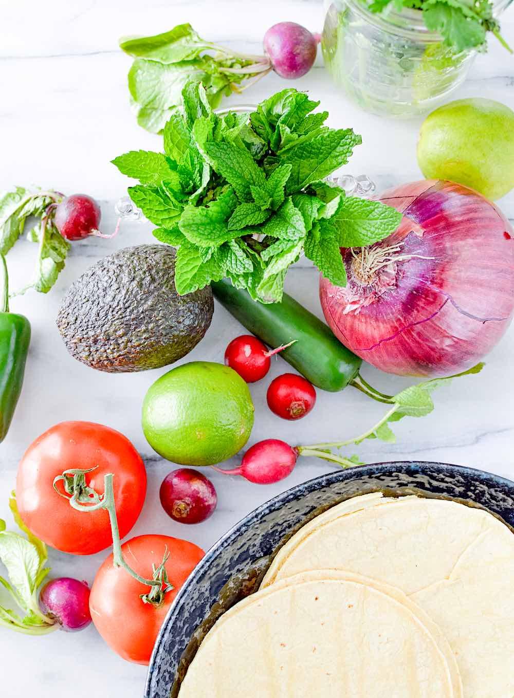 Overhead shot of ingredients for salpicon de pollo including onion, tomato, radishes, jalapeno, mint and cilantro.