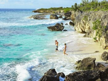 Couple entering water to go snorkeling in Bonaire.