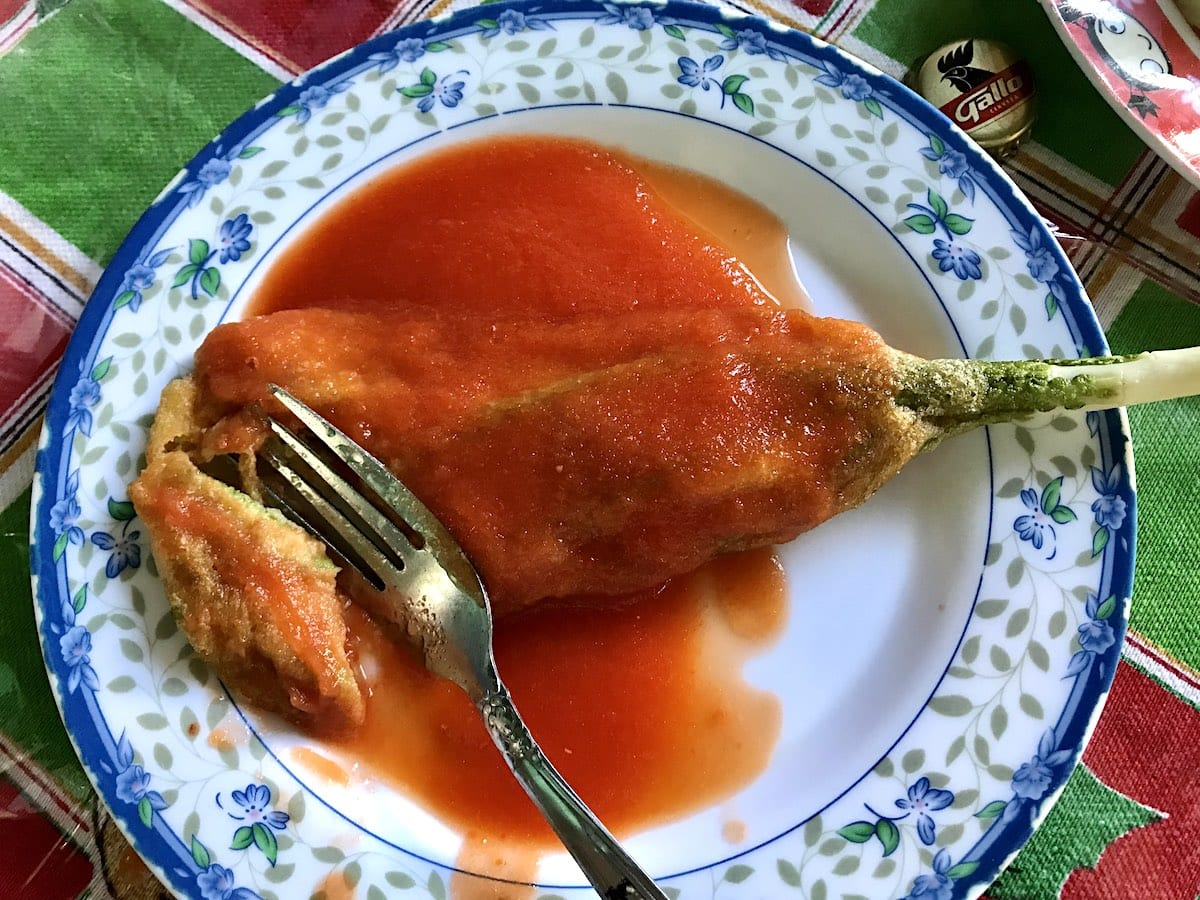 Guatemalan pacaya in salsa with a fork on a blue plate.