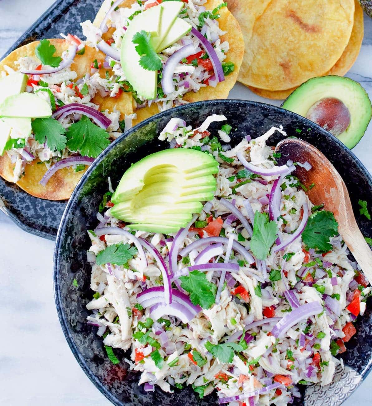 Chicken salpicon de pollo in a bowl and on tostadas.