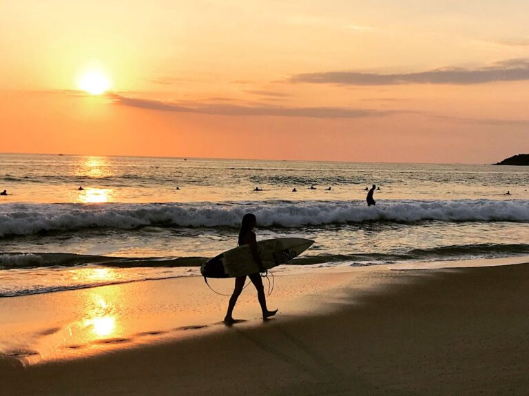 Surfer with board on a beach at sunset in Puerto Escondido, Oaxaca, Mexico.