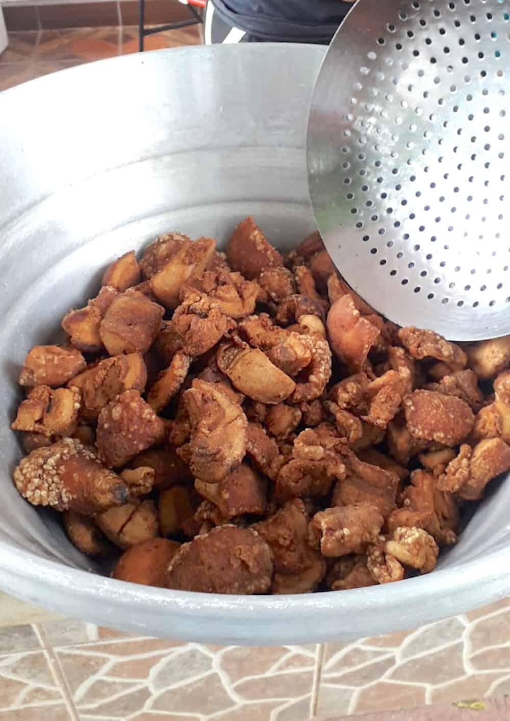 Crispy fried chicharrones in a metal pot.
