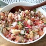Traditional Guatemalan chojin radish and chicharrones salad in a white bowl.