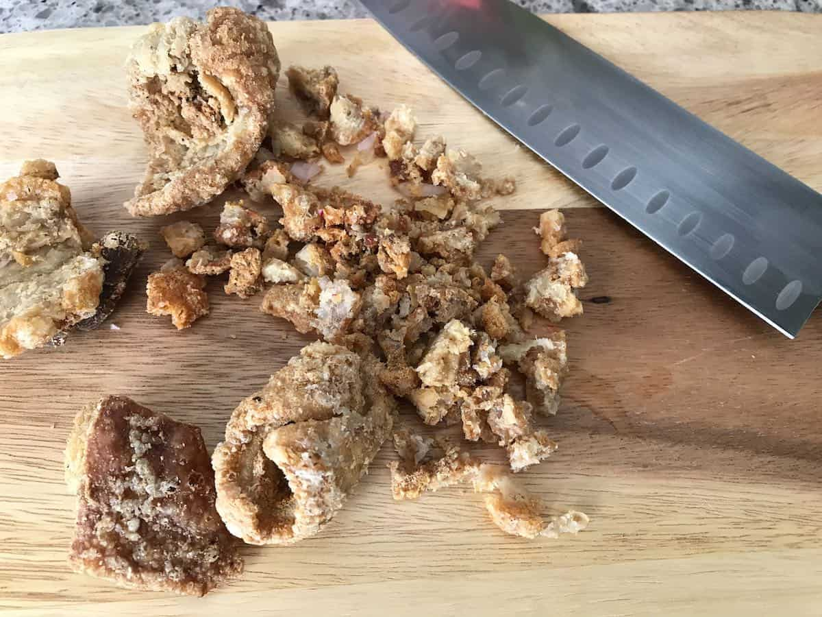 Chopping chicharrones with a knife on a wooden board.