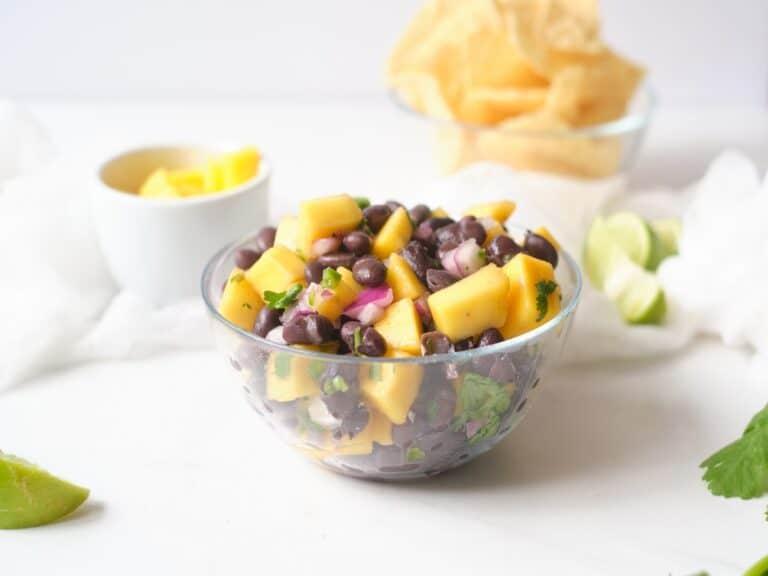 Clear bowl of mango black bean salsa on a white table.