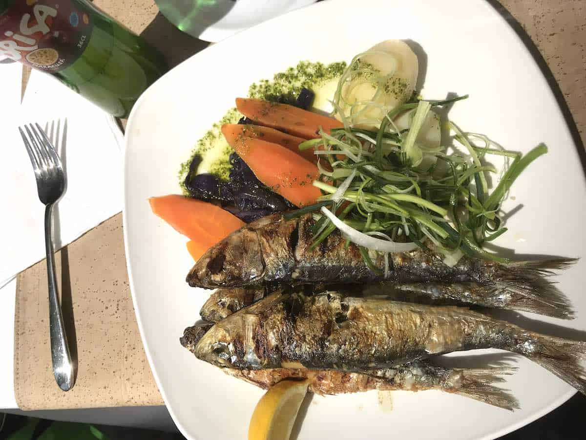 Grilled sardines on a white plate in Lisbon.
