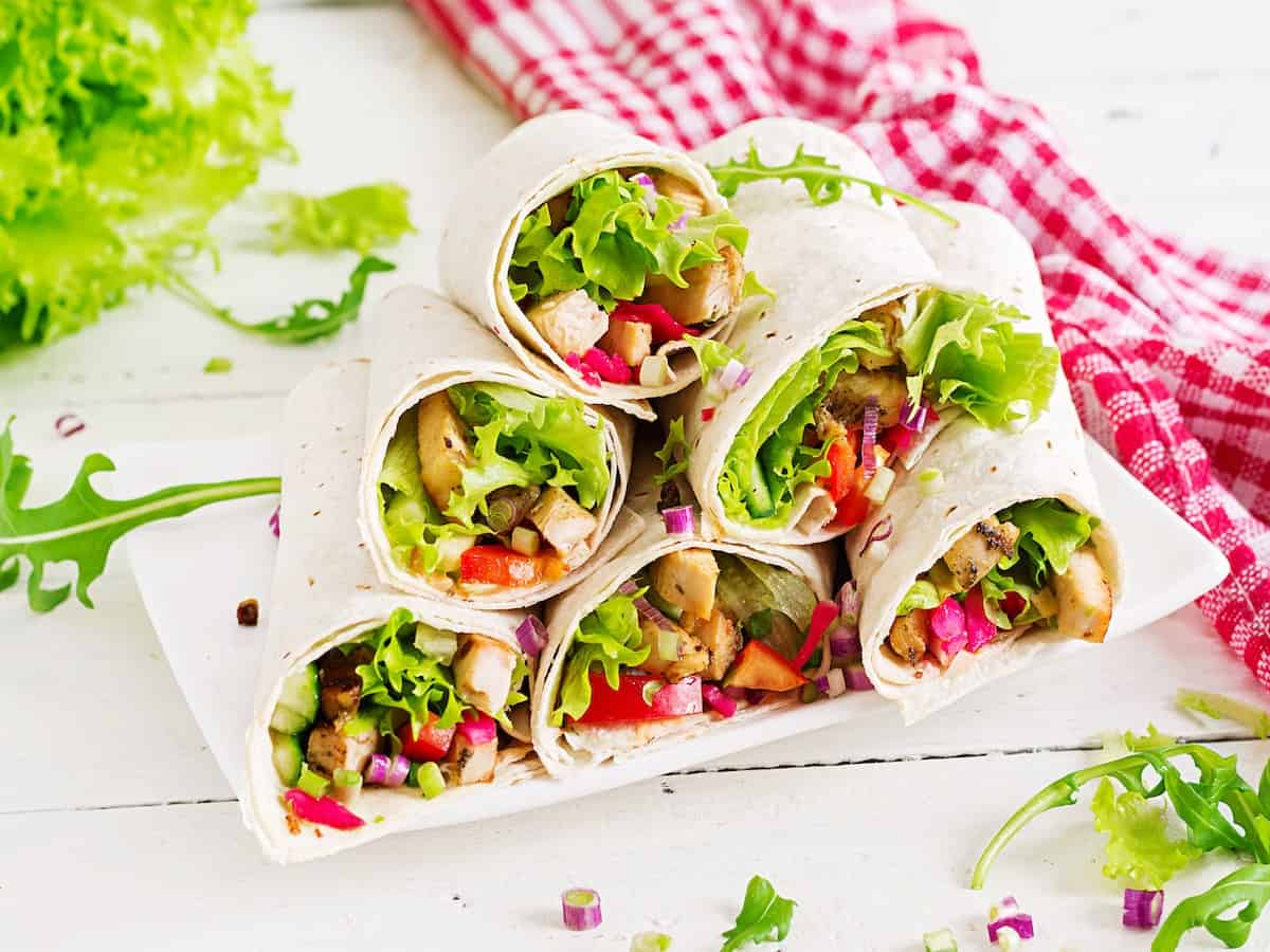 A stack of wrap sandwiches with a red gingham napkin.